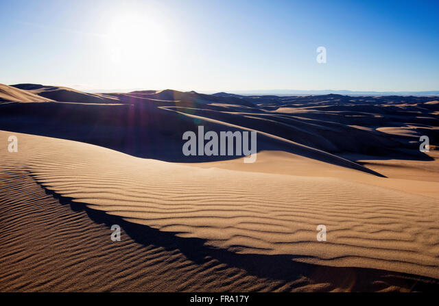 Sun shining over desert sand dunes in Great Sand Dunes National Park, Colorado, USA. - Stock Image