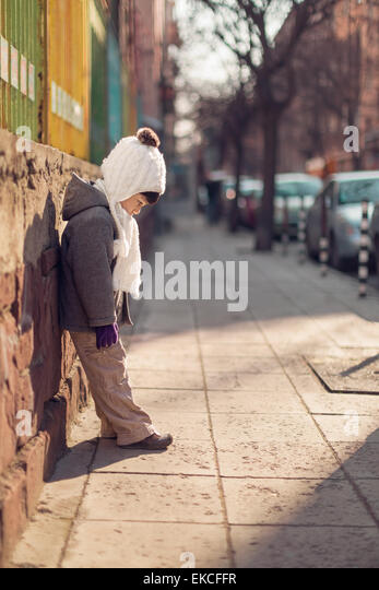 Boy leaning against a wall looking down at pavement - Stock Image