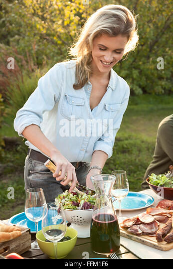 Young woman mixing salad on garden party - Stock Image