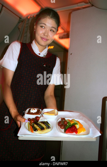 China Beijing Air China airlines onboard meal food tray fruit salad dessert service Asian woman flight attendant - Stock Image