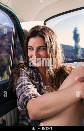 Portrait of young woman in back seat of car - Stock Image