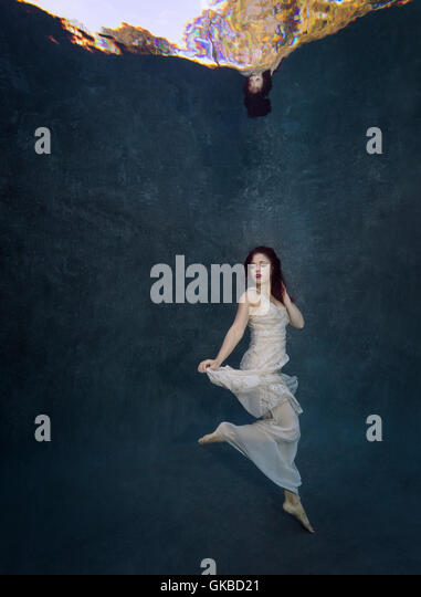 Young redhead in a white dress underwater, Virginia Beach, VA - Stock Image