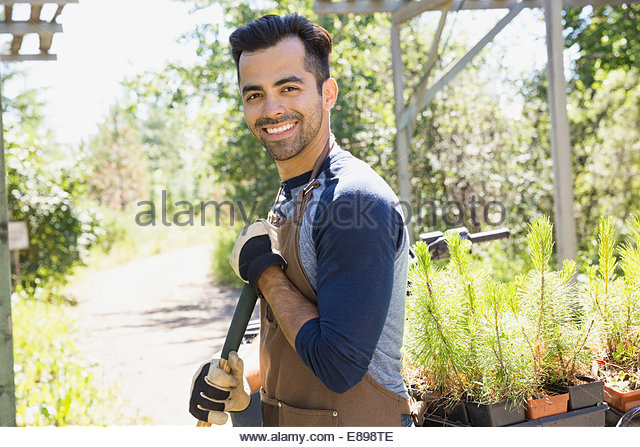 Portrait of smiling worker at plant nursery - Stock Image
