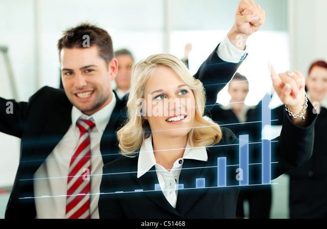 Business - presentation within a team; a female colleague shows graph or chart on screen - Stock Image