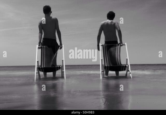 Walking on the Mediterranean sea and carrying our seats - Stock Image