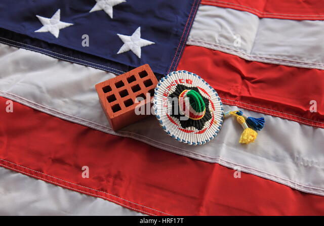 Clay brick and mexican sombrero on USA flag as symbol for the anounced 'trump wall' Photo by Willy Matheisl - Stock Image