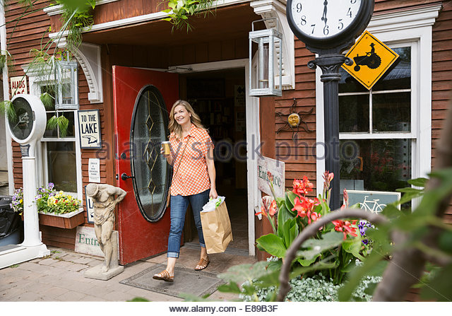 Woman with coffee and shopping bag leaving market - Stock-Bilder