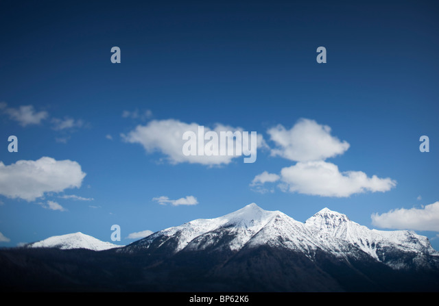 Snow capped mountains and sky with clouds - Stock Image