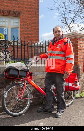 Village postman with his bike, Plumtree, Nottinghamshire, England, UK - Stock Image