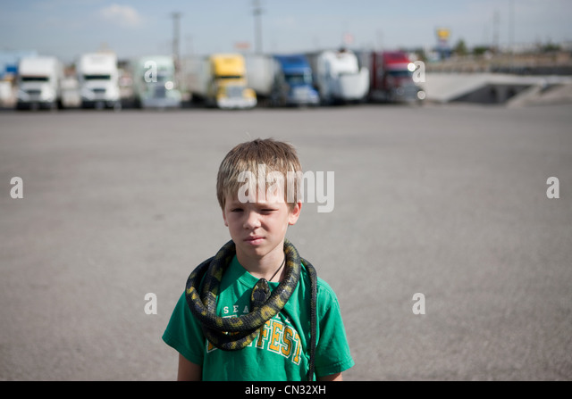 Boy with snake around his neck - Stock Image