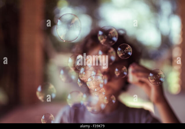 Boy blowing bubbles - Stock Image