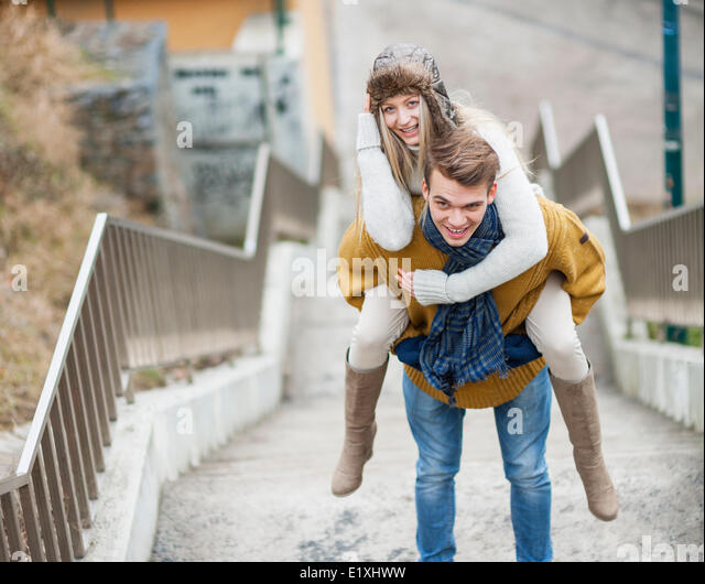 Portrait of smiling woman being piggybacked by man on stairway - Stock Image