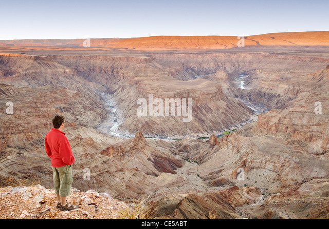 A man stands looking out across the Fish River Canyon in southern Namibia at dawn. - Stock Image