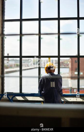 Construction worker standing by window - Stock-Bilder