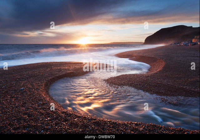 River Winniford flowing into the sea at Seatown Beach with the cliffs of Golden Cap in the Distance. Jurassic Coast. - Stock Image