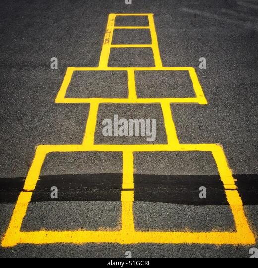A series of yellow squares FB form a gameboard on the cement playground - Stock-Bilder
