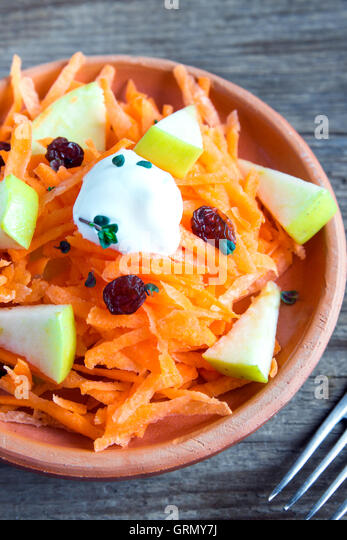 Carrot and apple salad with raisins, yogurt and herbs in rustic ceramic bowl close up - Stock Image