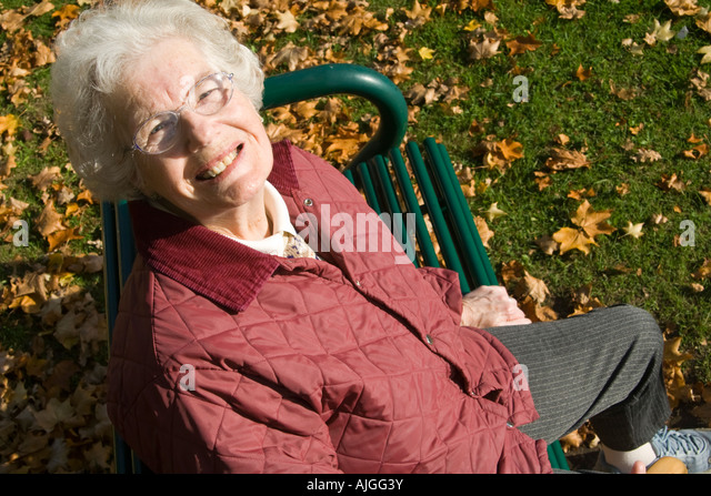 Elderly lady sitting on a seat and looking-up - Stock-Bilder