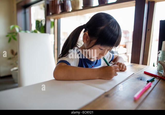 Girl with pigtails sitting at a table, drawing with felt tip pens. - Stock Image