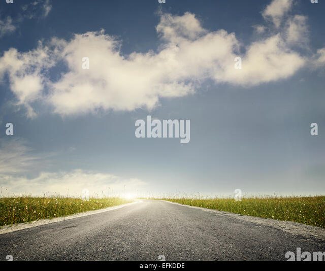 Wide road and green meadow at blue cloudy sky background - Stock Image