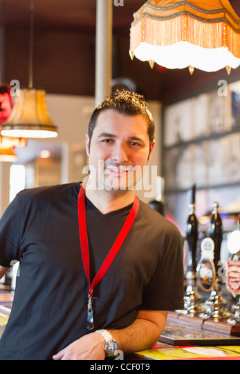 Portrait of smiling pub manager - Stock Image