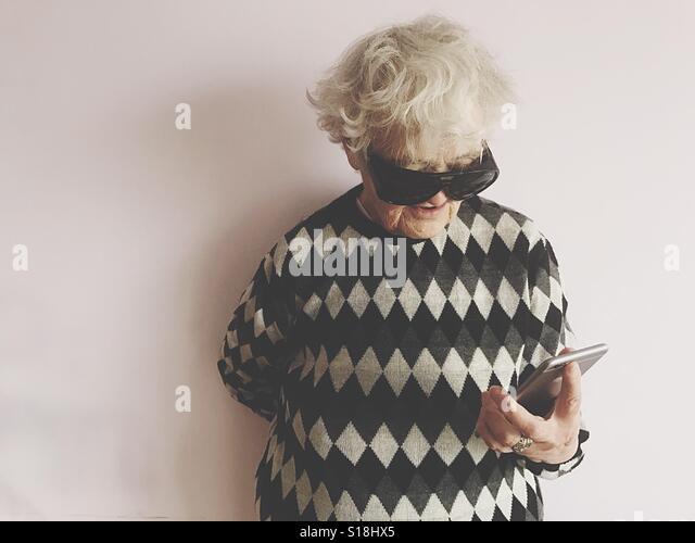 Elderly lady holding phone - Stock-Bilder