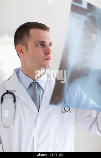 Doctor taking a look at x-ray photograph - Stock Image