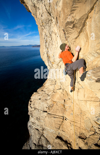 Climber reaches for hand hold. - Stock Image