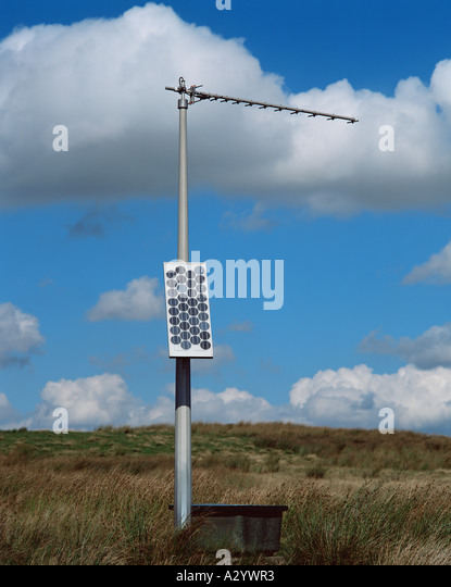 Solar panel on antenna pole in field - Stock Image