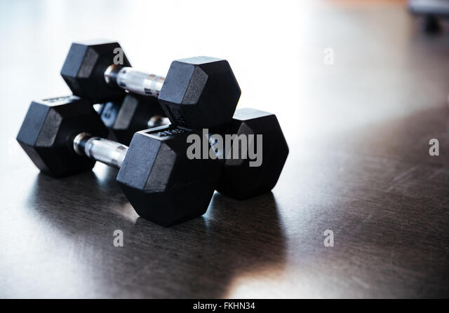 Closeup of three metal dumbbells on the floor in gym - Stock-Bilder
