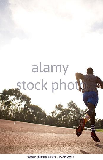African American man running on track - Stock-Bilder