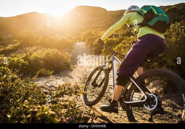 Young woman mountain biking on dirt track, Monterey, California, USA - Stock Image