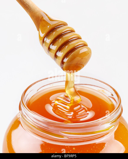 Honey dipper and full honey pot isolated on a white background - Stock Image