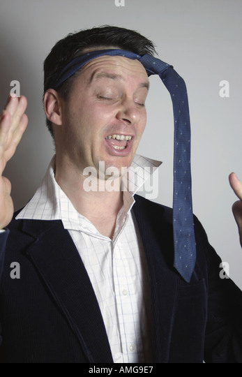 Man drunk at party with tie around his head - Stock Image