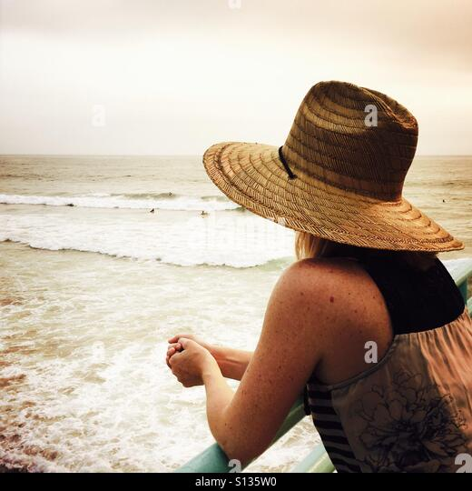 A young women in a hat looks out to the ocean on the Manhattan Beach pier. Manhattan Beach, California USA. - Stock Image