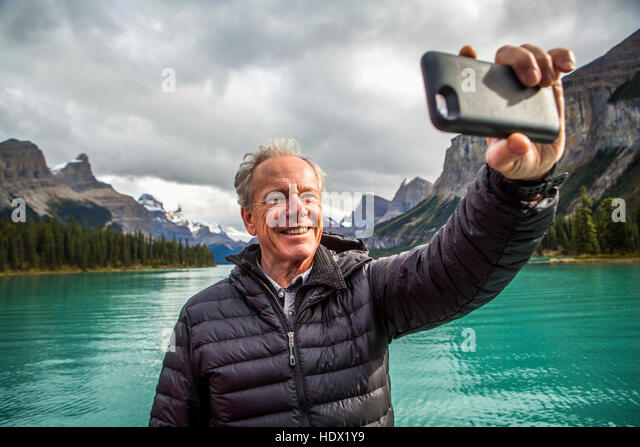 Caucasian man posing for cell phone selfie near mountain lake - Stock Image