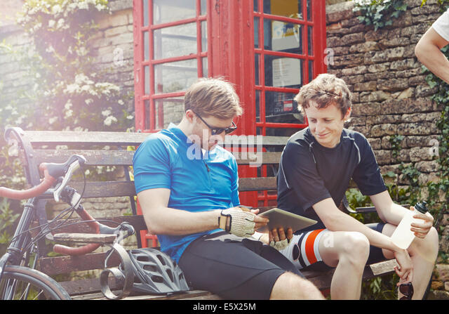 Cyclists using digital tablet by red telephone box, Cotswolds, UK - Stock Image