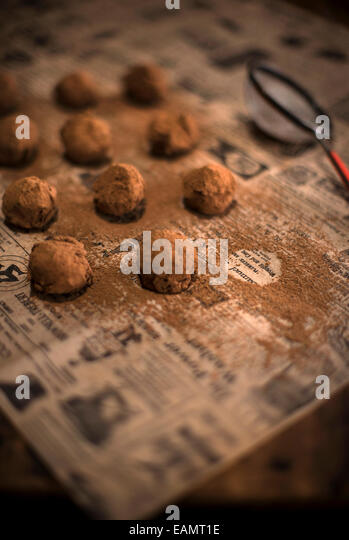 Rows of chocolate truffles with cocoa dusting, sitting on antique newspaper and a rustic wood surface. - Stock Image