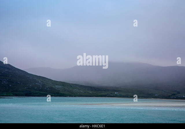 Fog rolling over tranquil mountains and ocean, Golden Road, Harris, Outer Hebrides - Stock Image