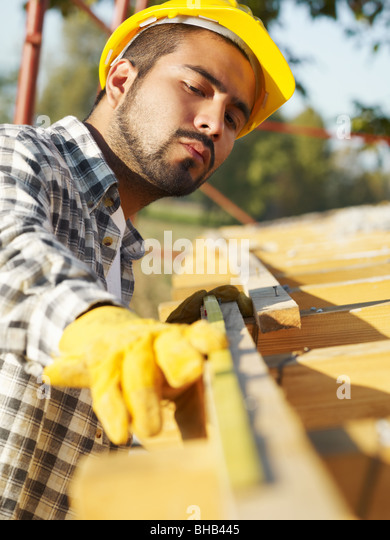 latin american construction worker on house roof with measuring tape. - Stock-Bilder