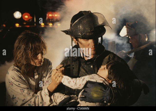 Firefighter carrying a boy during rescue operation - Stock Image
