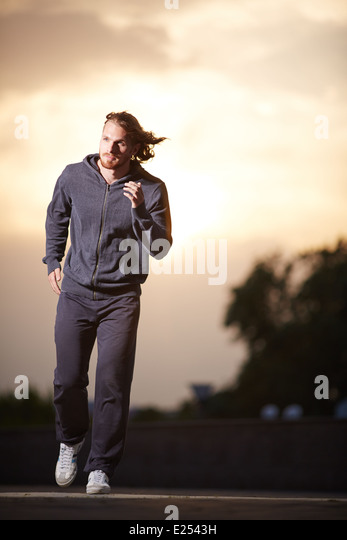 Portrait of young sportsman running in the evening - Stock Image