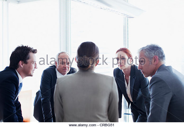 Business people leaning in circle and talking - Stock Image