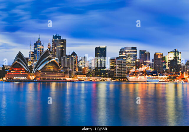 Cityscape of Sydney city CBD across Harbour at sunrise reflecting bright lights of skyscrapers and major landmark - Stock Image