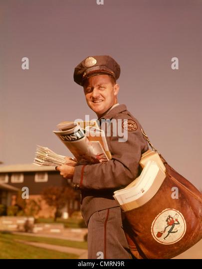 1960 1960s SMILING MAILMAN HOLDING MAIL MAILBAG LETTERS UNIFORM DELIVERY MAN MAILMEN POSTAL SERVICE MEN RETRO - Stock Image