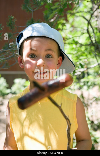 A young boy holding a cooked sausage on a stick - Stock-Bilder