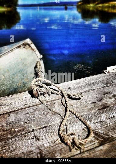 Metal canoe tied to boat dock with lake in distance - Stock Image