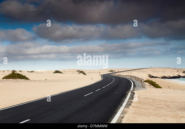 Road through sand dunes, Canary Islands - Stock Image
