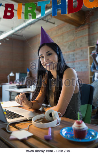 Portrait smiling businesswoman celebrating birthday at laptop - Stock Image