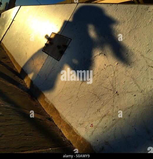 Shadow of woman running along the East River park in Manhattan. - Stock-Bilder